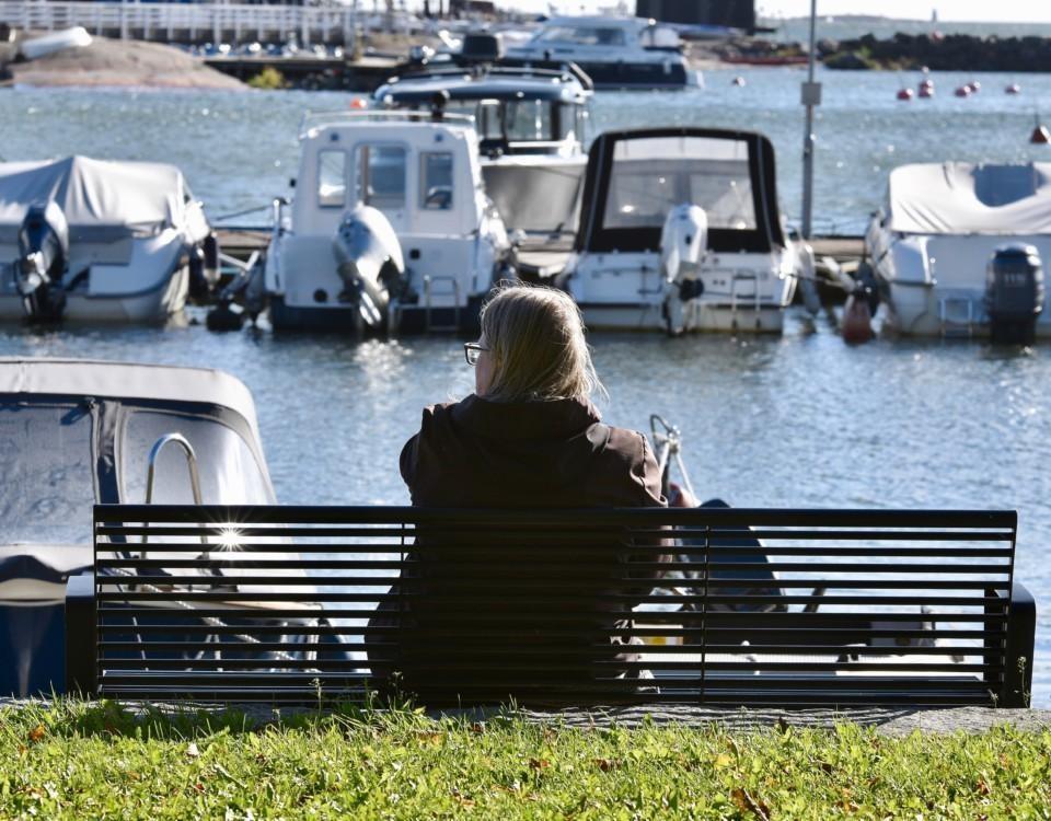En person sitter på en bänk och blickar ut över en båthamn.