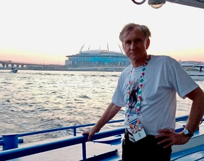 En man står på en båt och lutar sig mot relingen.