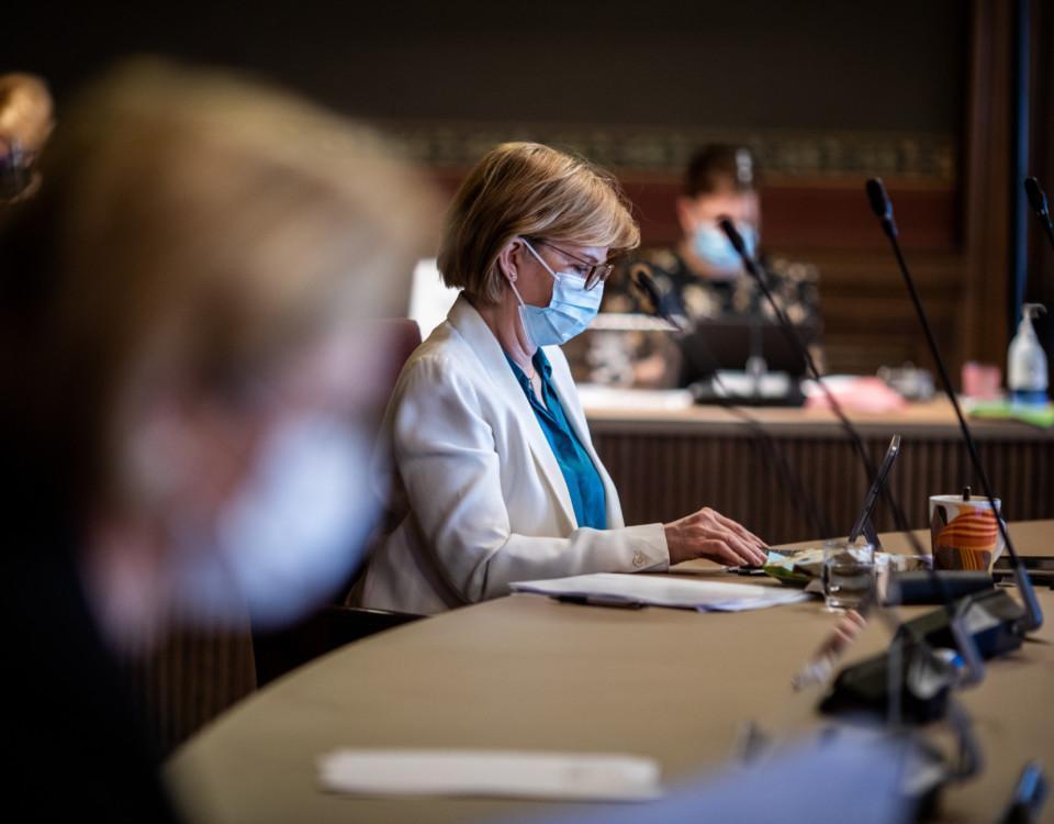 En kvinna sitter vid ett bord med papper framför sig. Hon bär munskydd.