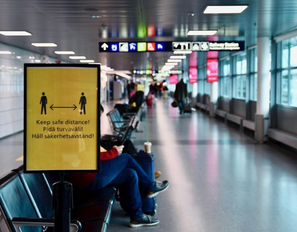En vänthall på ett flygfält. En gul skylt påminner om att man bör hålla säkerhetsavstånd.