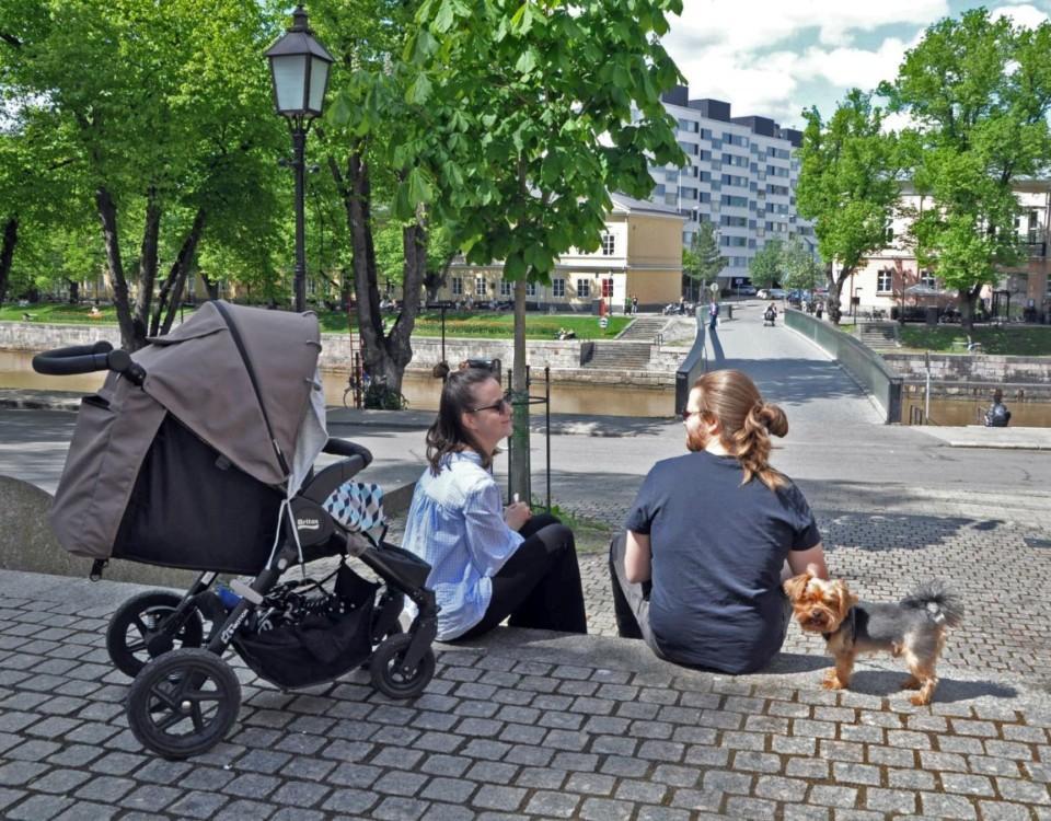 Kvinna och man med barn och hund kopplar av vid åstranden