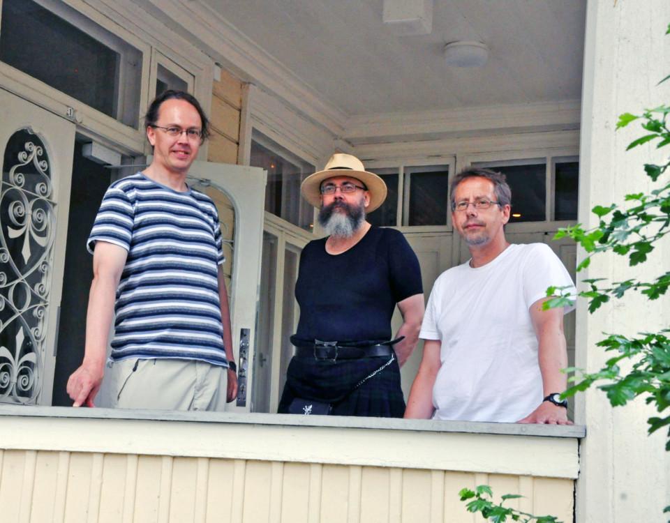 Tre män står på en terrass och tittar in i kameran.