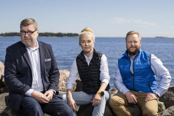 Topi Jurvanen, Michaela Lindström och Otto Kaukonen sitter tillsammans på klippor vid havet.