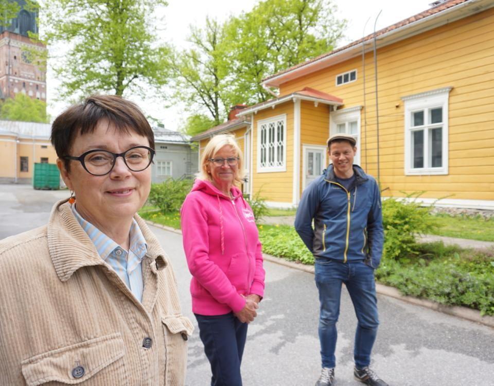 tre personer står vid en lång byggnad med ordentliga avstånd till varandra