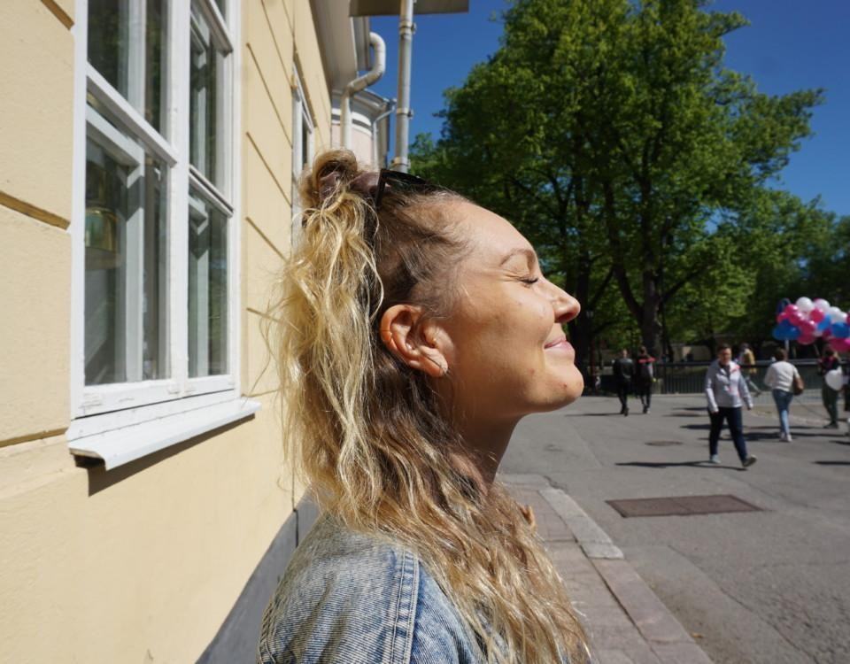 leende kvinna står vid en gul tegelvägg och blundar mot solen