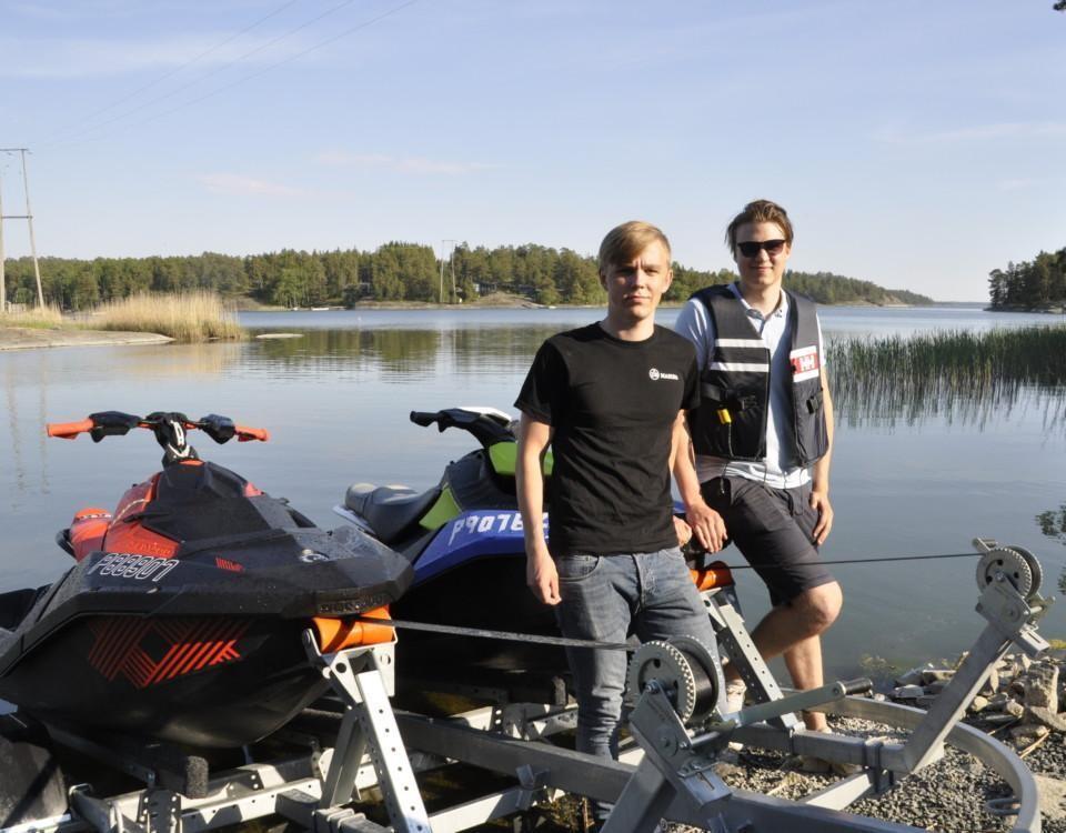 två unga män vid två vattenskotrar
