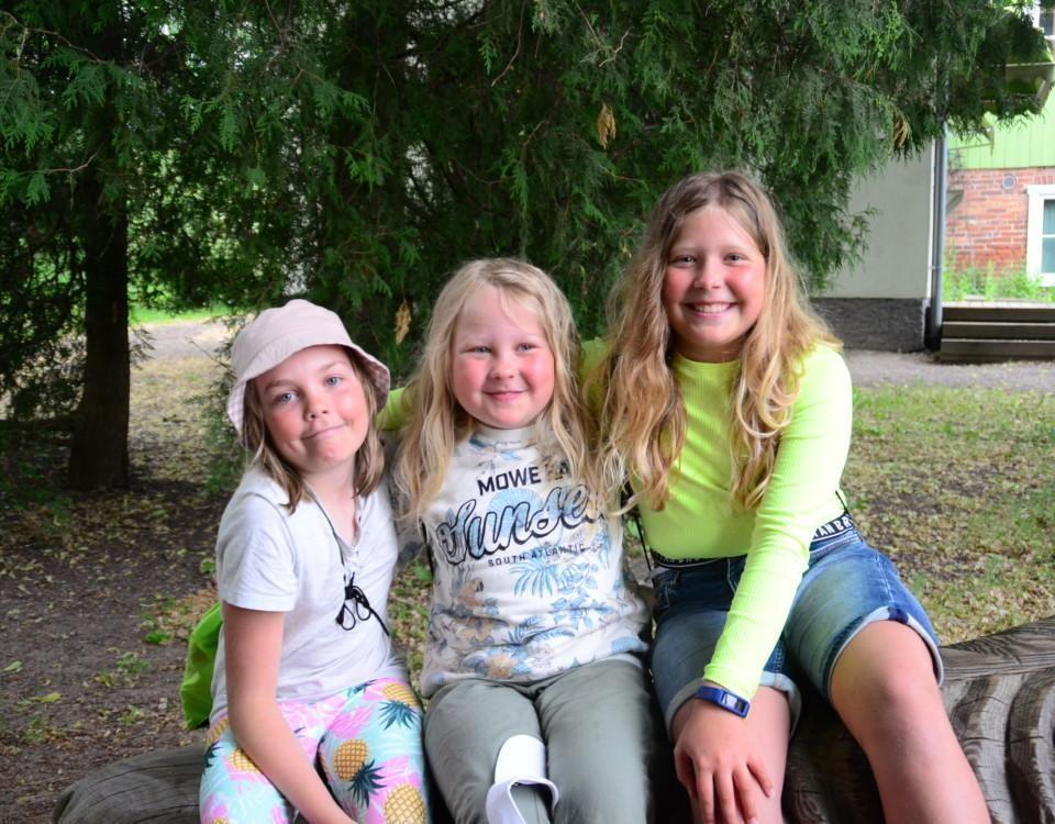 Tre flickor sitter på ett trälejon, de håller om varandra och ser glada ut.