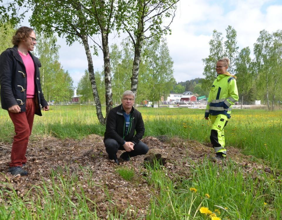 två män och en kvinna inspekterar trädgårdsavfall