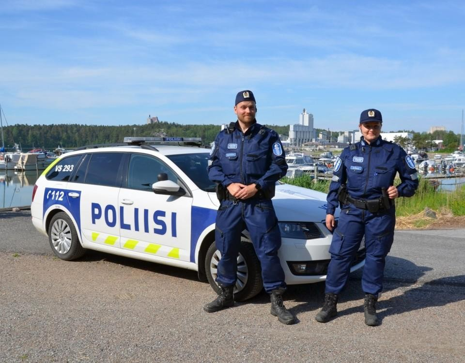två poliser framför en polisbil i skärgårdsmiljö