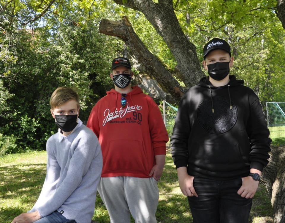 Tre pojkar med munskydd vid ett träd