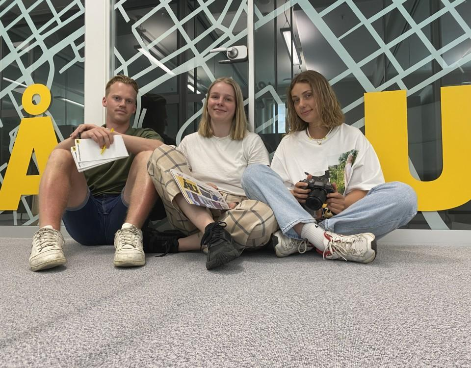 Sommarreportarna 2021 sitter alla tre på golvet mellan bokstäverna Å och U. Alla tittar in i kameran.