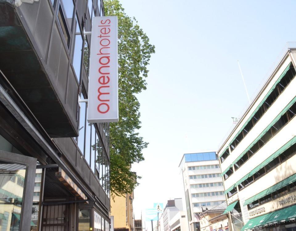 En skylt vid en gata där det står Omenahotelli.
