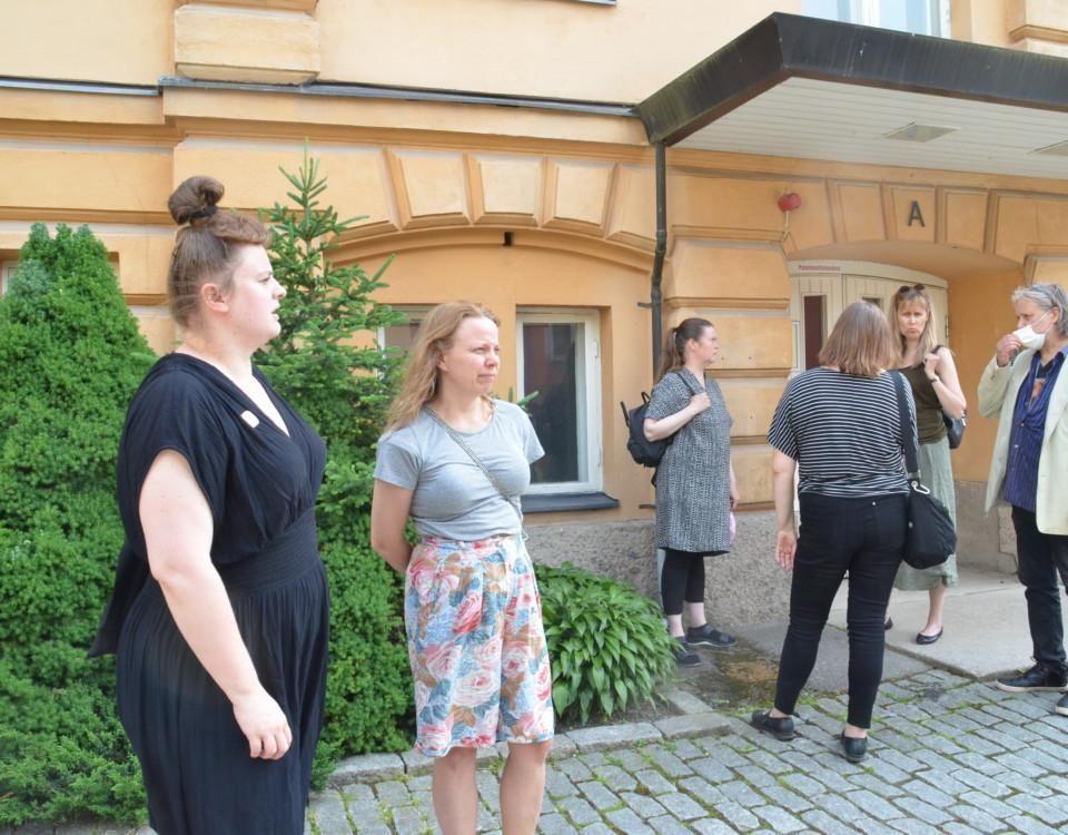 En grupp människor står utanför en byggnad och diskuterar. I förgrunden står två kvinnor och ser fundersamma ut.