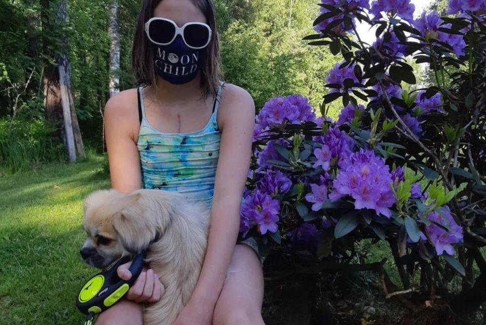 Flicka med hund. Hon bär munskydd och mörka solglasögon.