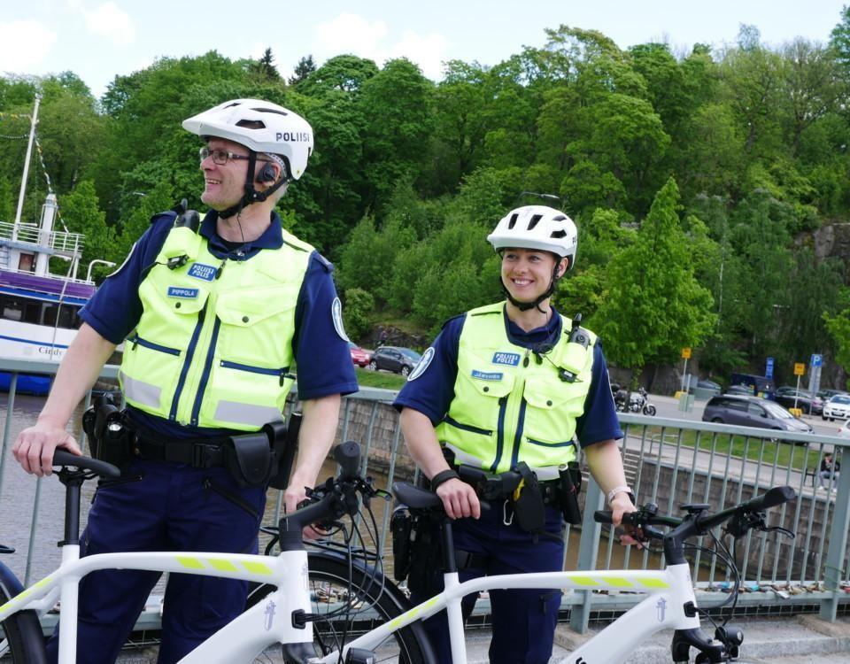 två poliser och cyklar och träd bakom dem