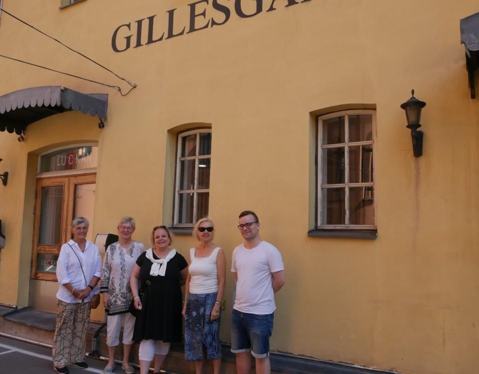 """Fem personer står utanför Gillesgårdens gula fasad. På bilen syns texten """"Gillesgården"""" ovanför"""