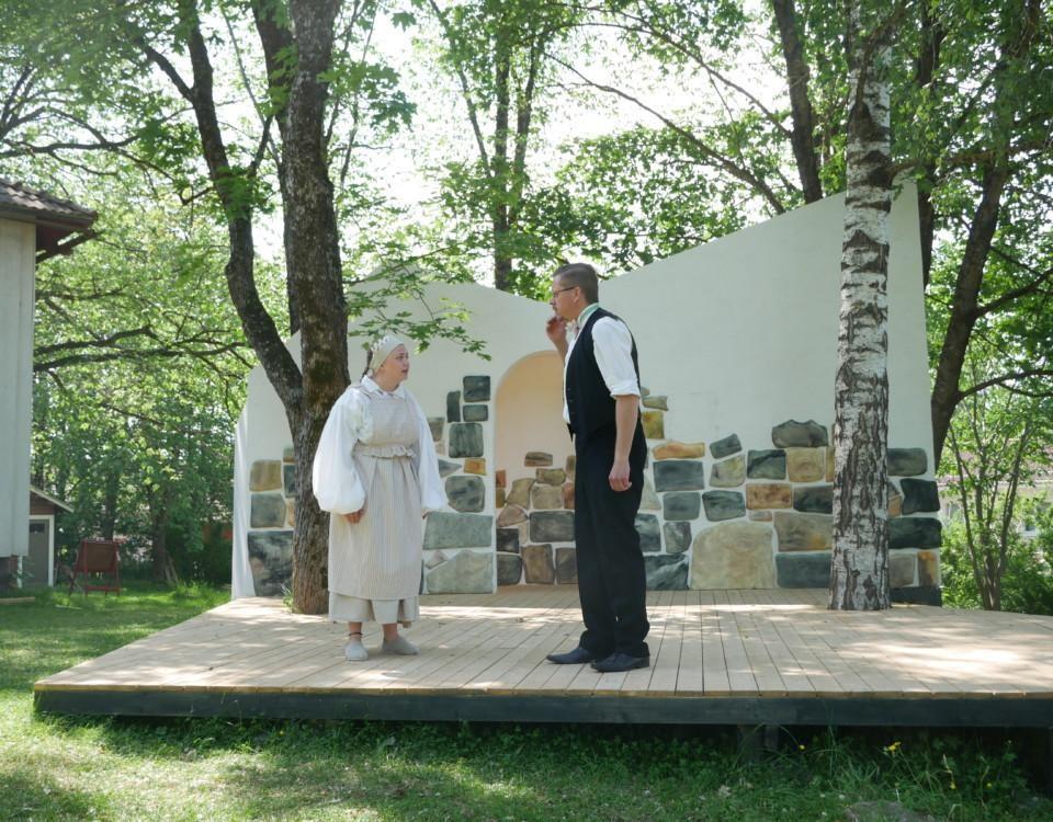 Två skådespelare, en man och en kvinna står på en scen utomhus. De är riktade mot varandra och talar.