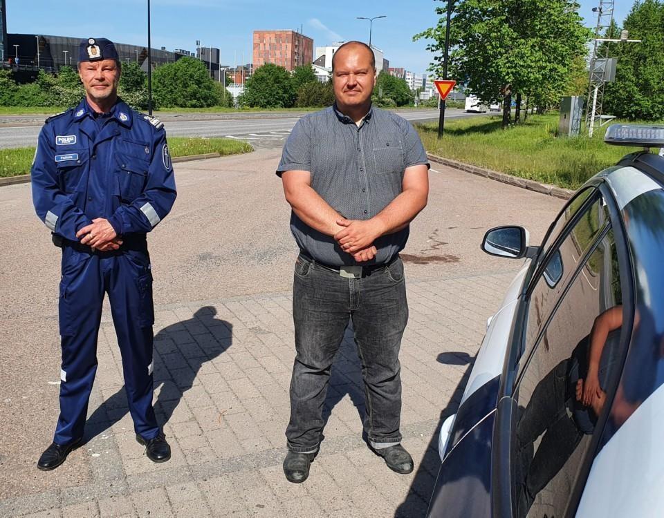 Peltola iklädd polisuniform och Heiskanen i skorta och jeans poserar framför en polisbil med motorvägen i bakgrunden.