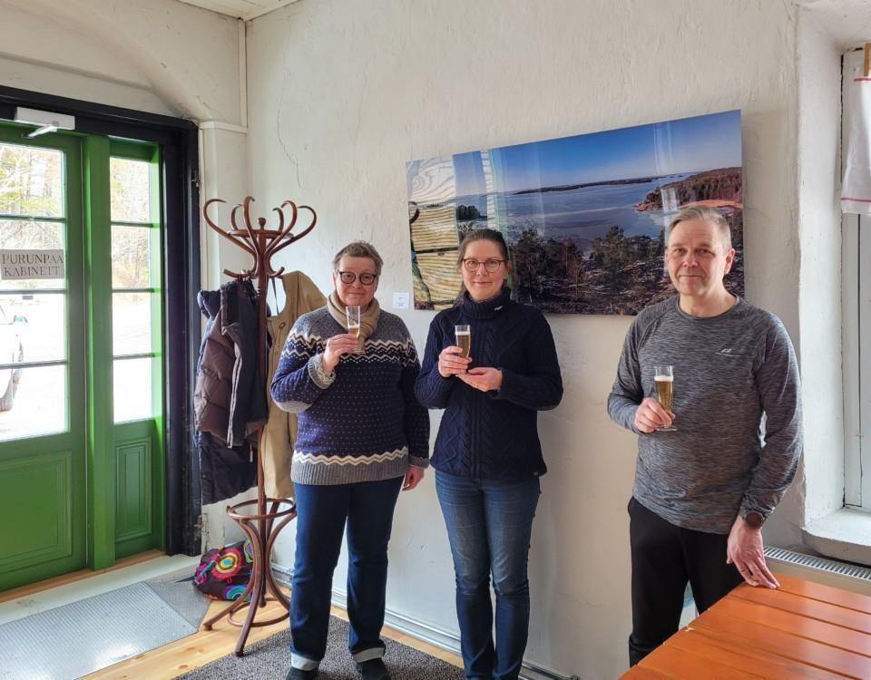 Tre personer vid ett fotografi som hänger på väggen