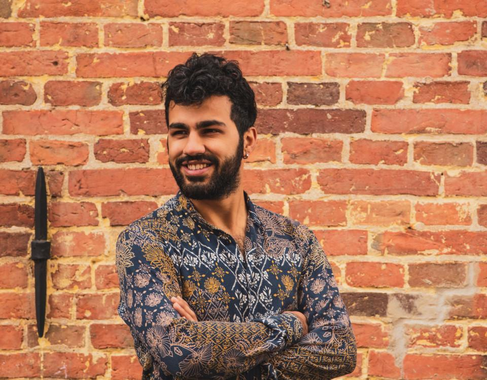 en leende man står mot en röd tegelvägg