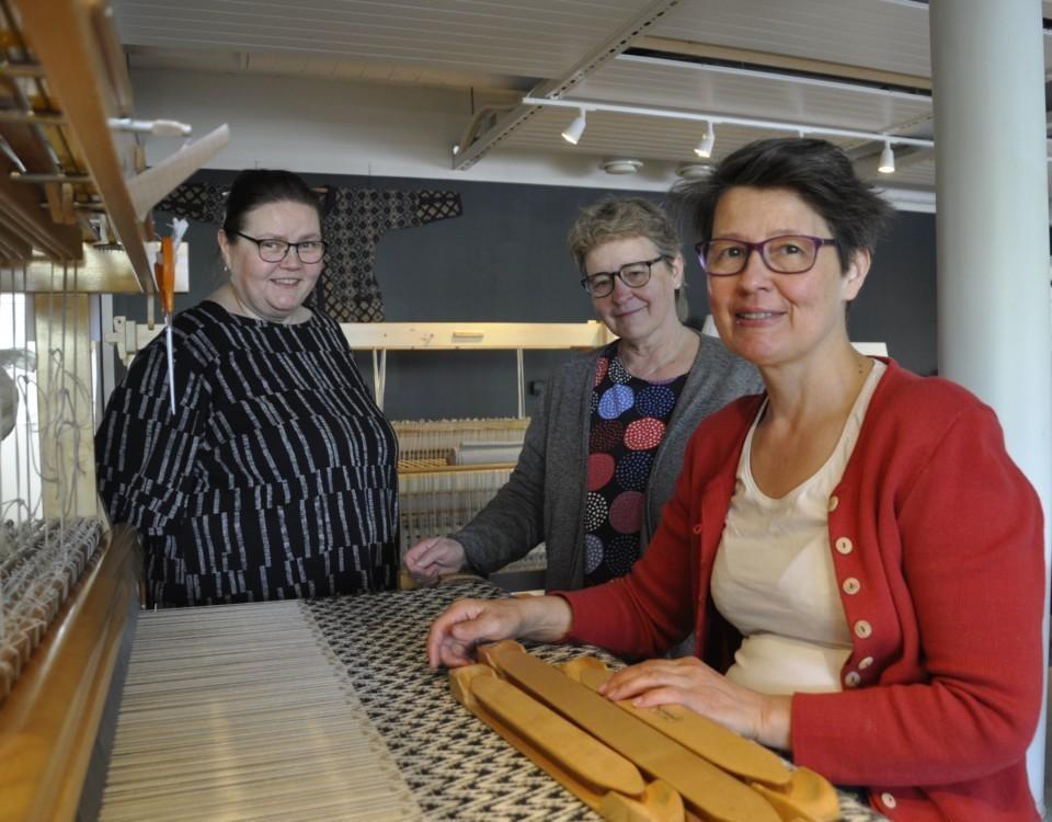 tre damer vid en vävstol