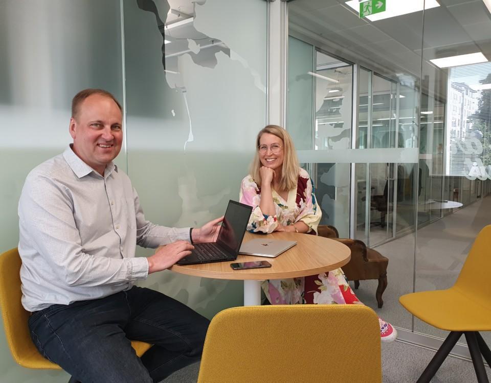 man och kvinna vid ett mötesbord, dator mellan dem
