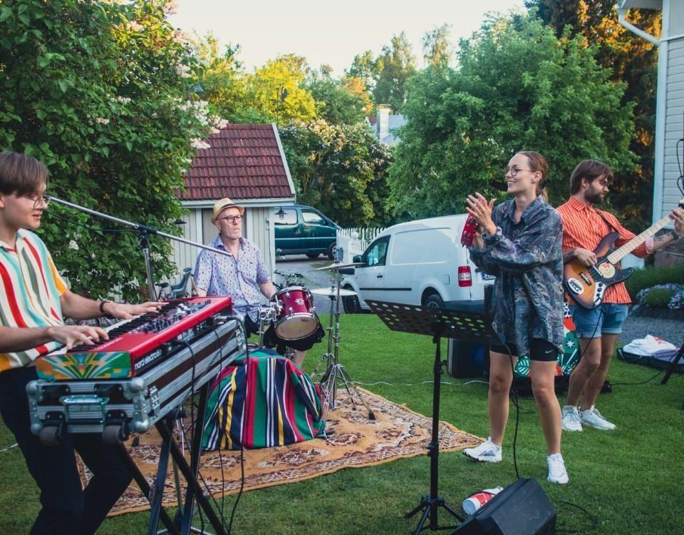 fyra människor spelar musik i en trädgård