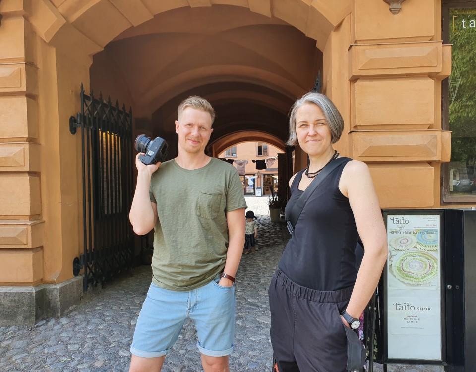 man med kamera i handen och kvinna klädd i svart
