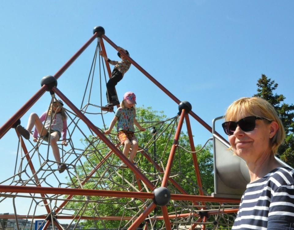 Kvinna övervakar barn i hög klätterställning