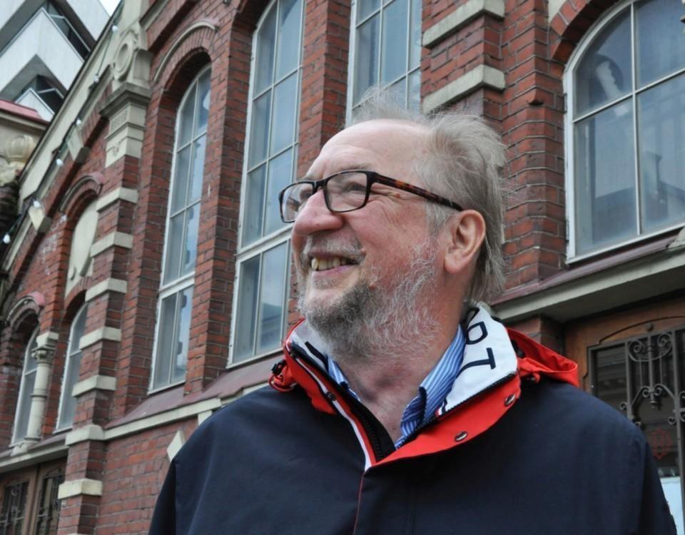 Skäggig medelålders man står framför gammal tegelbyggnad