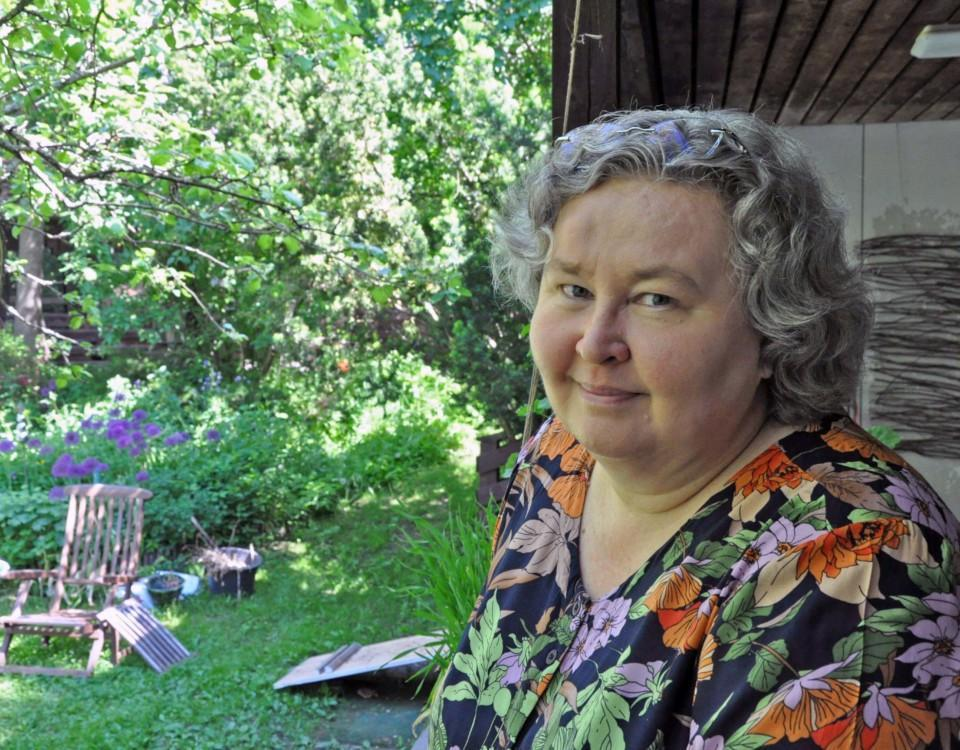 Kvinna i lummig trädgård