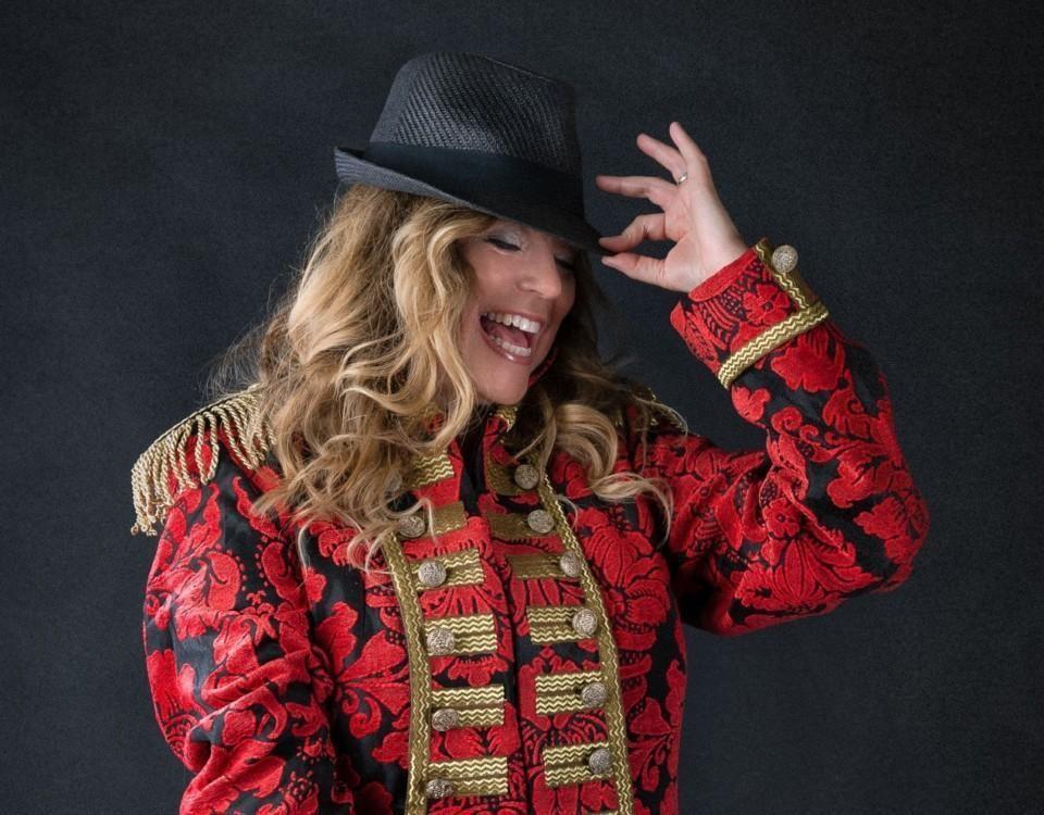 Susann Sonntag står iklädd cirkusdirektörkostym och skrattar.