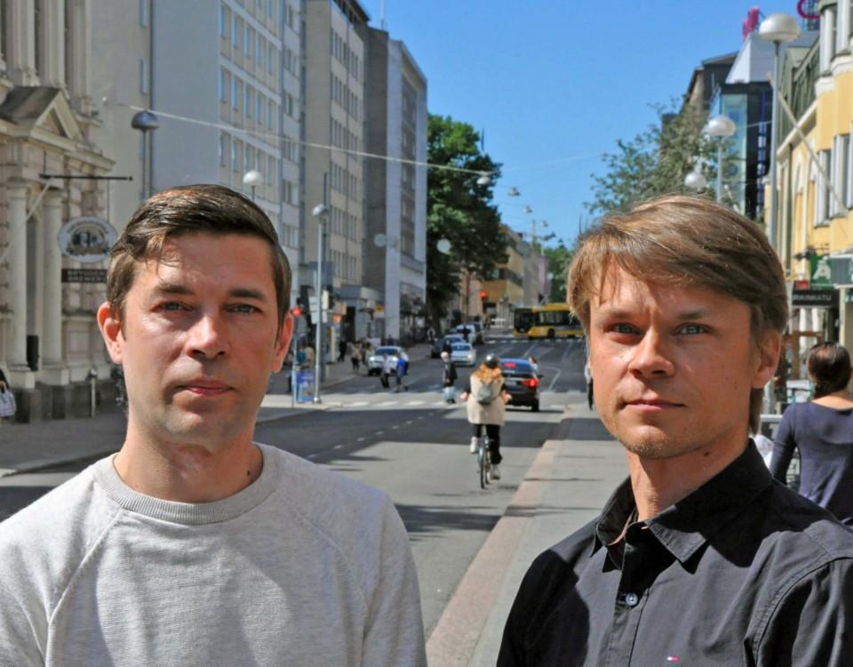 Två män står på trottoar