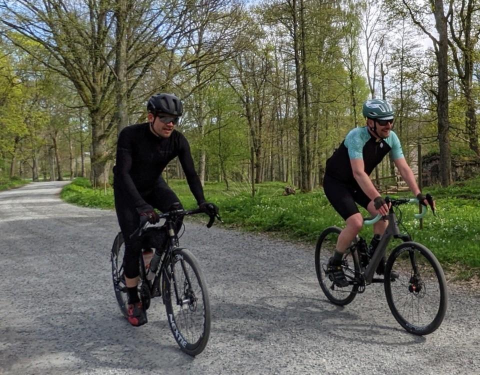 Två män cyklar på varsin cykel på grusväg, träd i bakgrunden