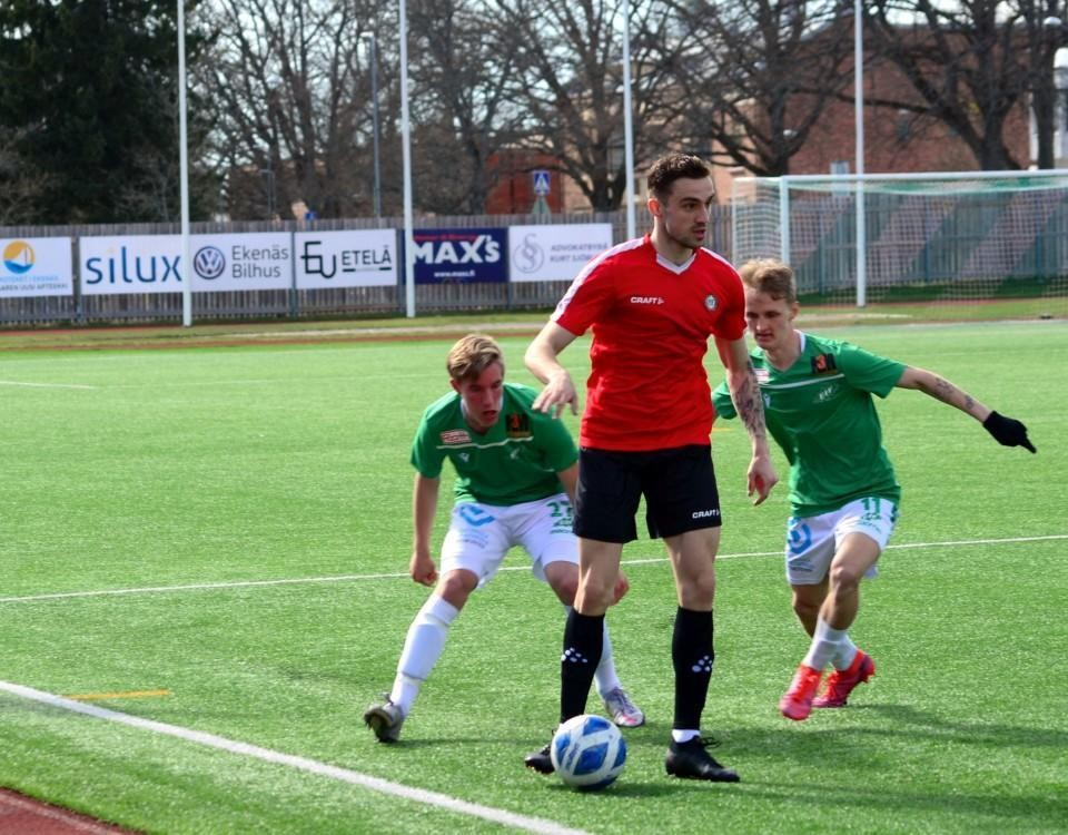 en fotbollsspelare skyddar bollen från två motståndare