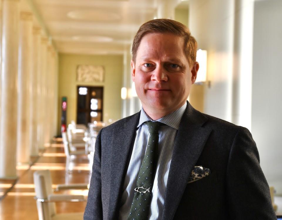 En man iklädd kostym står i en korridor och ler mot kameran.