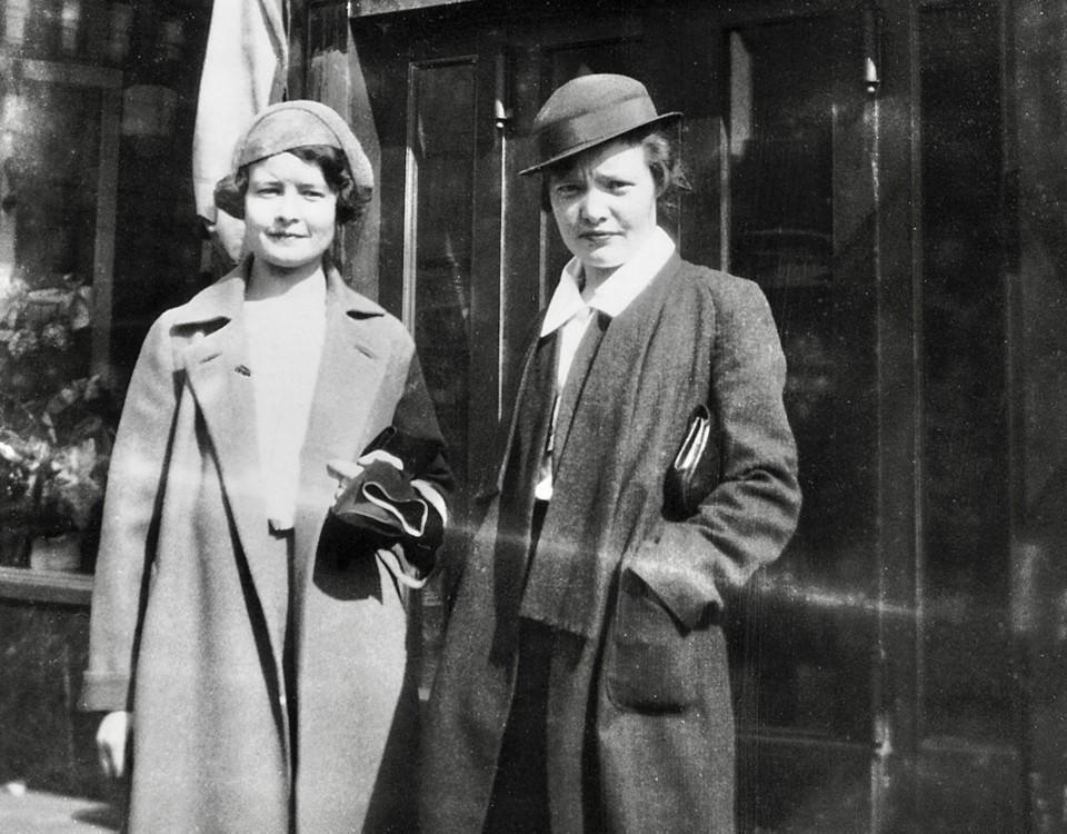 En svartvit bild där två kvinnor står på en gata.