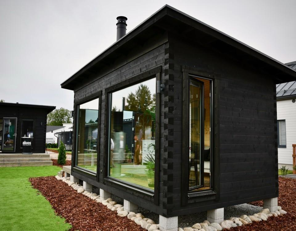 Ett litet mörkmålat hus.