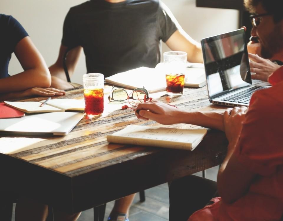 Människor som sitter runt ett bord och jobbar.
