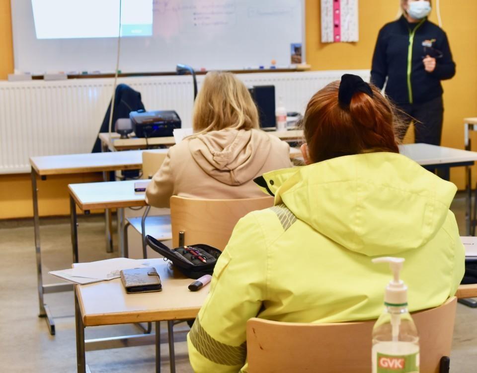 Skolelever sitter i ett klassrum vid pulpeter.