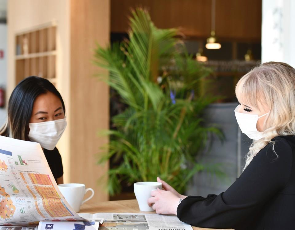 Två kvinnor sitter vid ett bord iklädda munskydd och tittar tillsammans i en tidning.