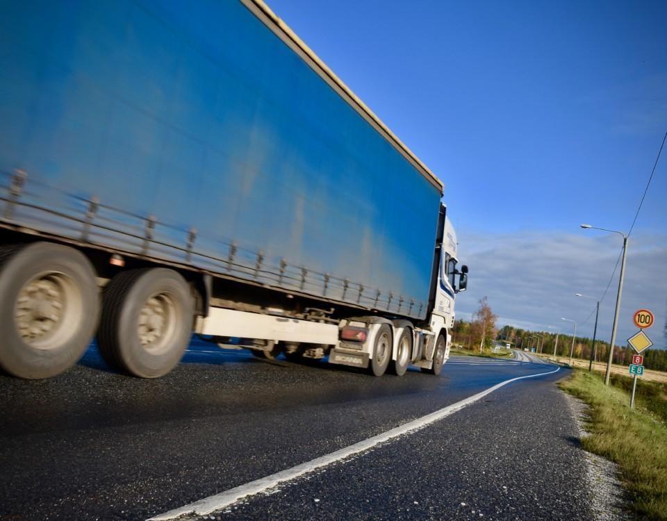 En lastbil kör på en landsväg.