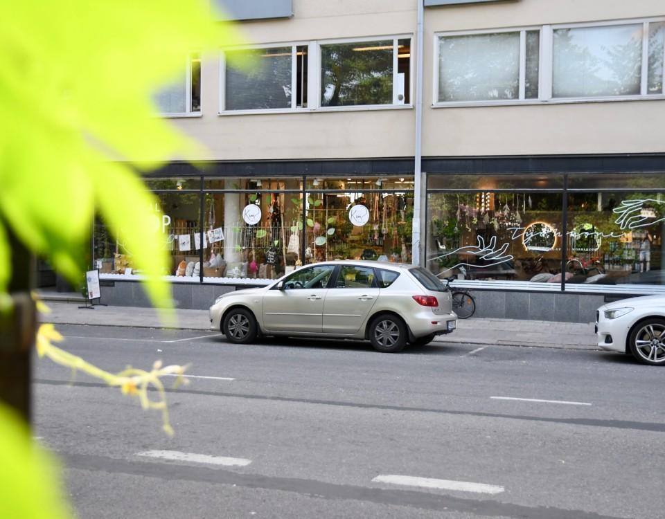 Bil på en gata med affärer.