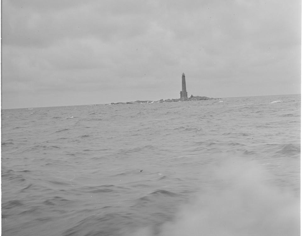 Ett svartvitt fotografi där Bengtskärs fyr skymtar på avstånd.