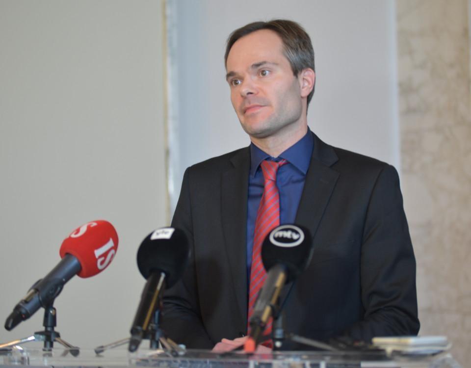En man iklädd kostym står framför en rad mikrofoner och talar.