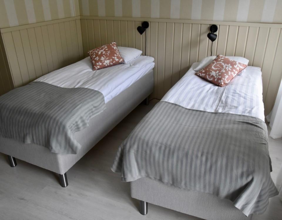 Två sängar i ett hotellrum.