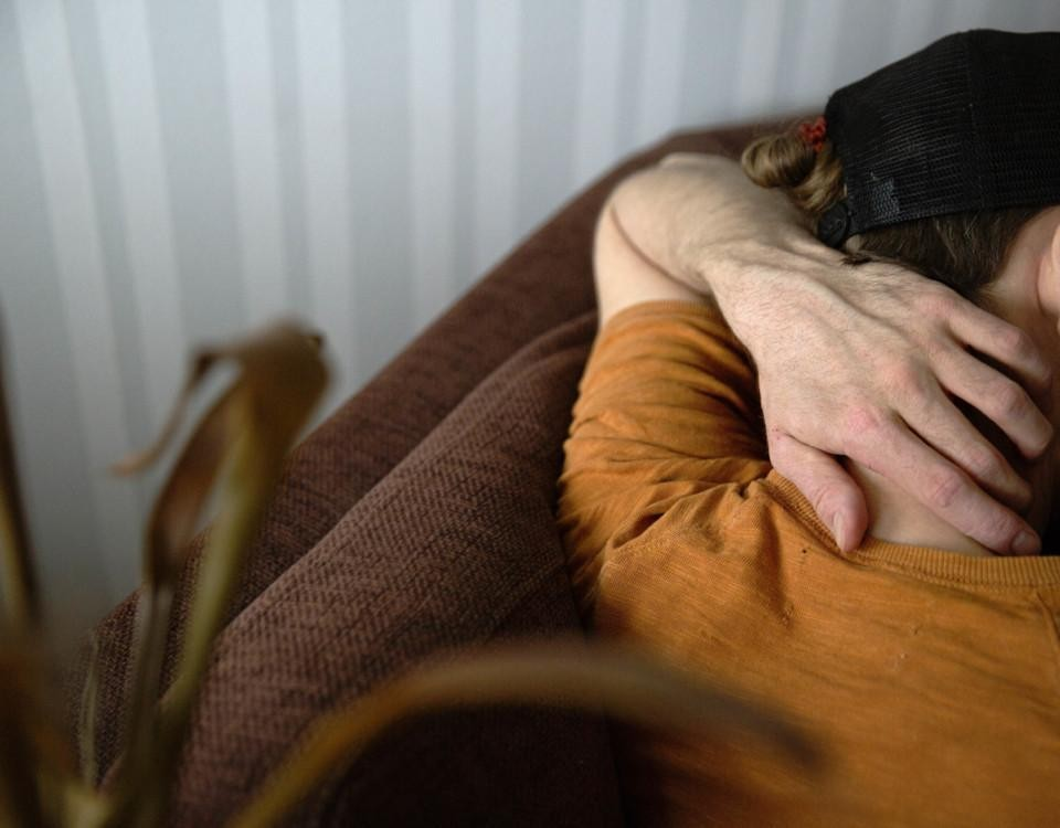 Illustrationsbild. En person sitter på en soffa.