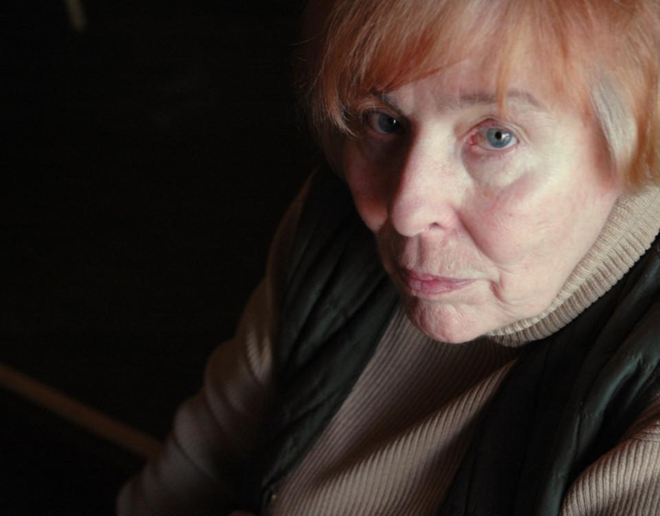 En äldre kvinna tittar in i kameran.