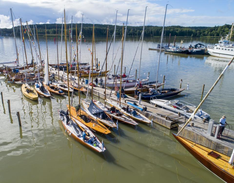 Flera klassiska segelbåtar vid en brygga, fotograferade uppifrån.