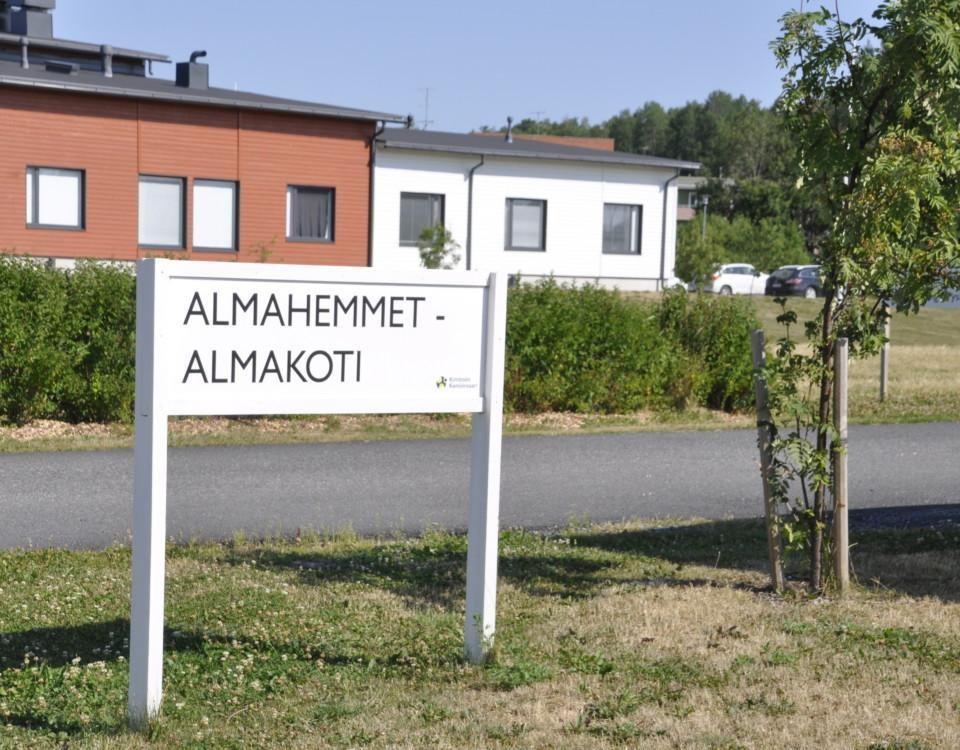 """Skylt med texten """"Almahemmet - Almakoti"""", rödvitthus i bakgrunden, grönt buskage runt omkring"""
